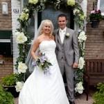 Bruid Marcella met haar man onder een bloemenboog in Amsterdam